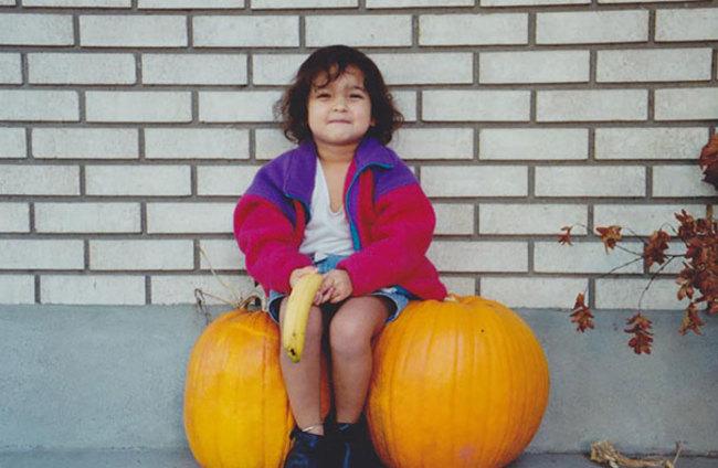 fotografía de una niña sentada entre dos calabazas sujetando un plátano entre sus piernas