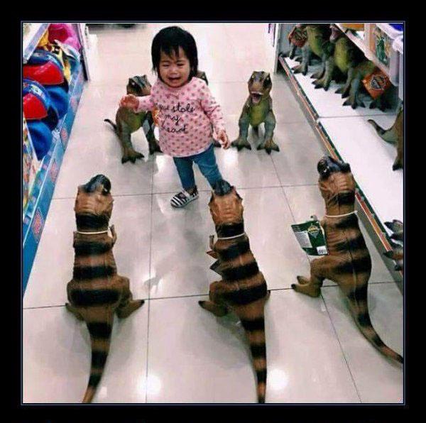 una pequeña niña rodeada de dinosaurios en un centro comercial