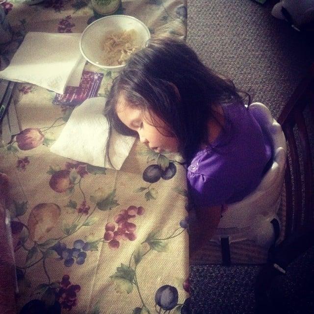 fotografía de una niña acostada sobre la mesa