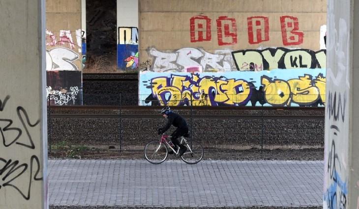 hombre transitando las calles de Alemania sobre su bicicleta cerca de las vías del ferrocarril