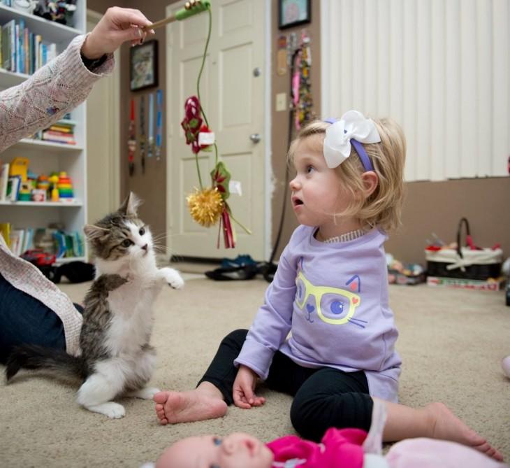 Scarlette niña sin un brazo jugando con su mamá y su gato de 3 patas