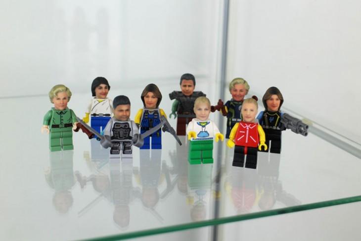 MONITOS DE LEGO CON CABEZAS HUMANAS EN REPISA DE VIDRIO