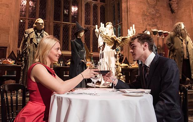 Personas brindando con dos copas en el Gran Salón de Hogwarts en Londres
