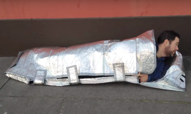 hombre acostado en el suelo con una bolsa para dormir