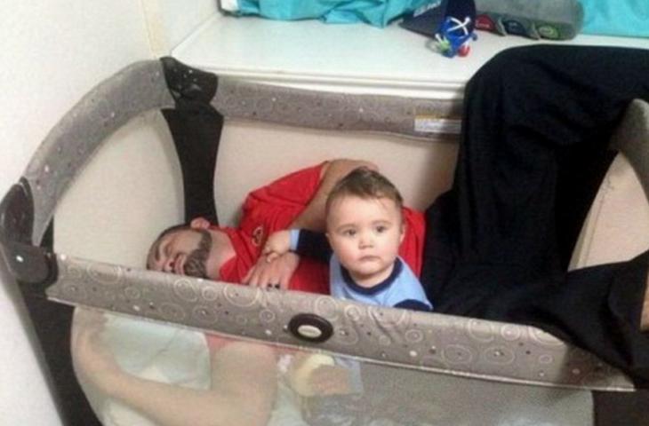 hombre dormido dentro de la cuna de su bebé
