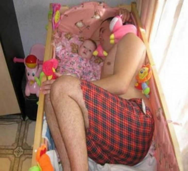 hombre dormido en la cuna de su bebé