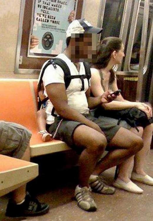 hombre sentado en el transporte público cargando a su bebé en la espalda
