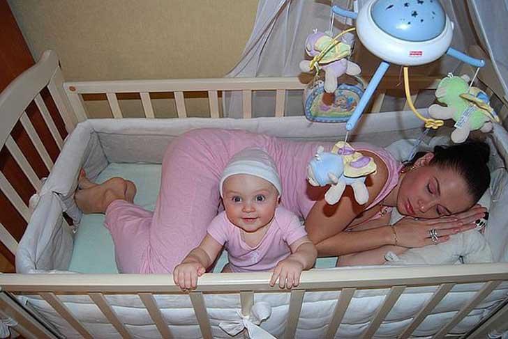mujer dormida a lado de su bebé sobre su cuna