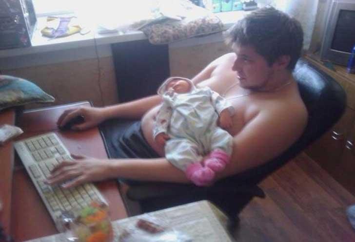 hombre sentado frente a una computadora con su hija sobre su estómago
