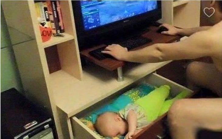 hombre en la computadora con su bebé dormido dentro de un cajón