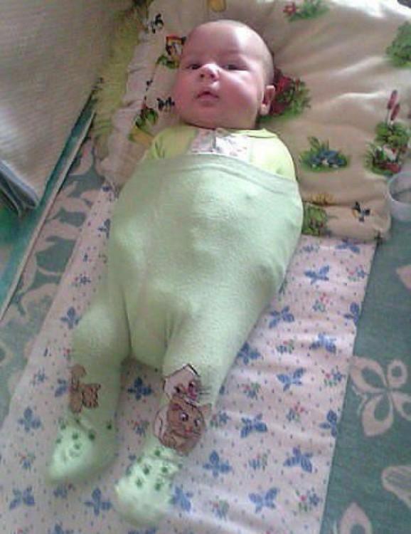 bebé acostado con un pantalón sosteniendo sus brazos