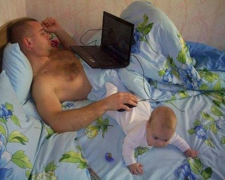 hombre acostado en la computadora usando a su bebé para colocar el ratón