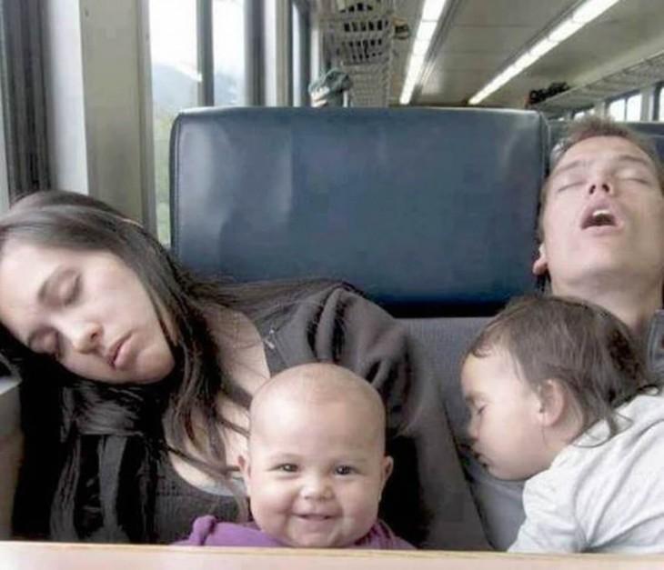 fotografía de dos padres dormidos con su hijas en un autobús