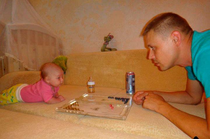 hombre frente a su hija con un juego de mesa entre ellos