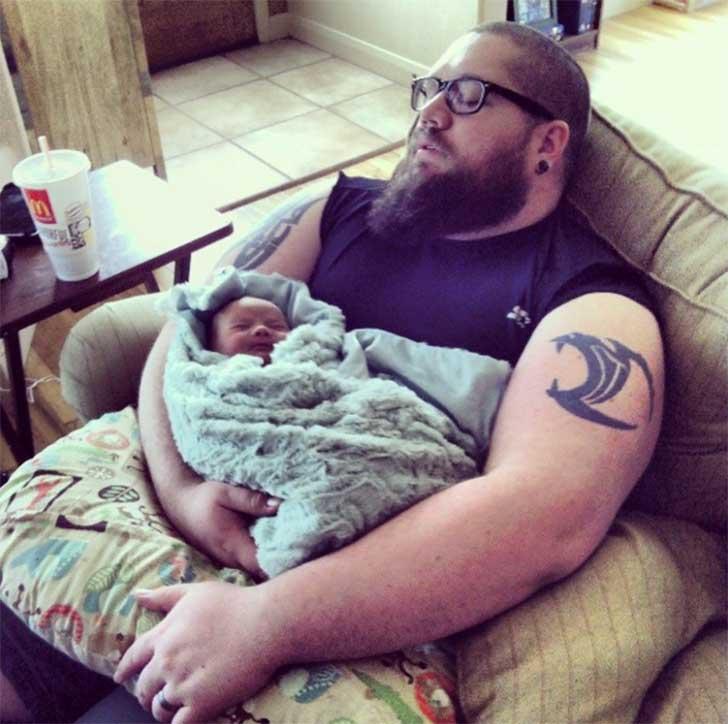 hombre sentado en un sillón dormido con su bebé en brazos