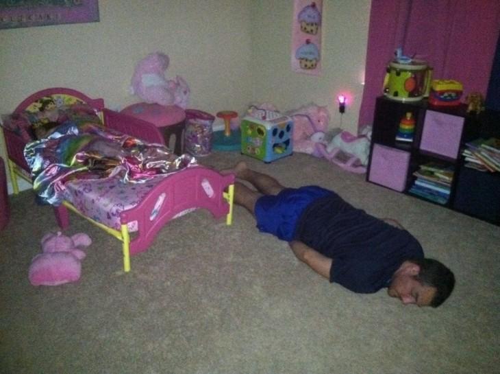 hombre dormido en el suelo de la habitación de su hija mientras ella duerme