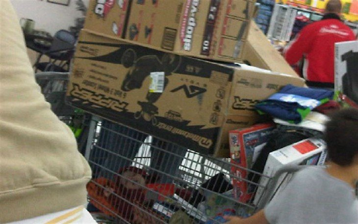 bebé dormido en el carrito del supermercado con las compras a su alrededor