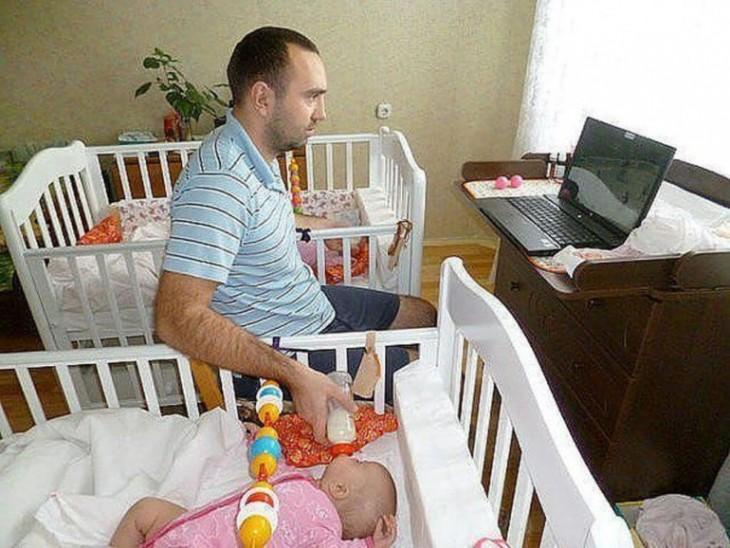 hombre dando de comer a sus dos bebés cada una en su cuna