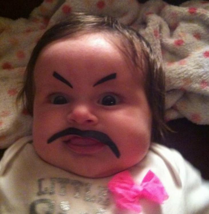 cara de una bebé con bigotes y cejas postizos