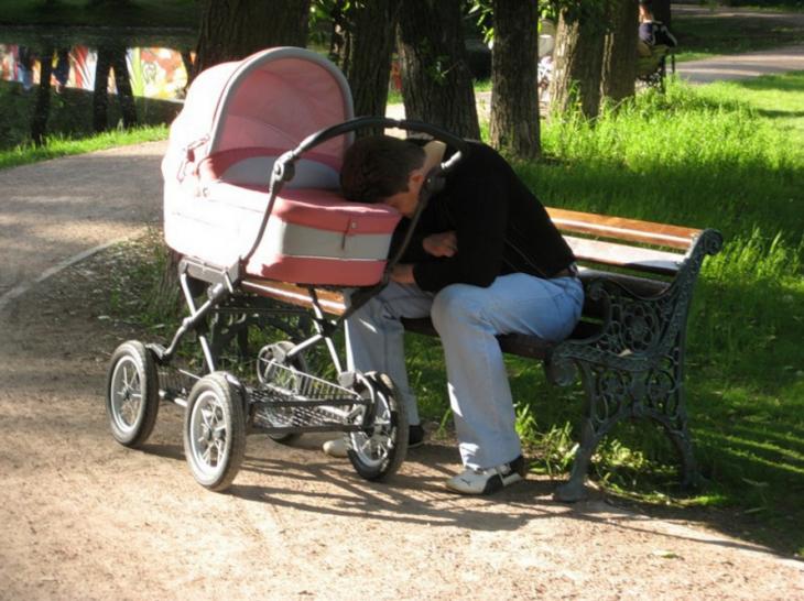 hombre dormido sobre la carriola de su bebé en un parque