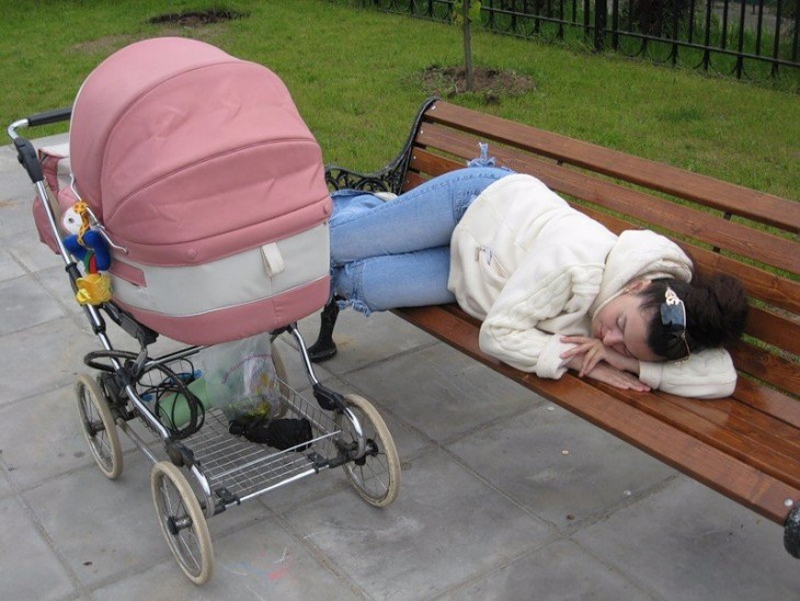 mujer dormida en la banca de un parque a lado de la carreola de su bebé