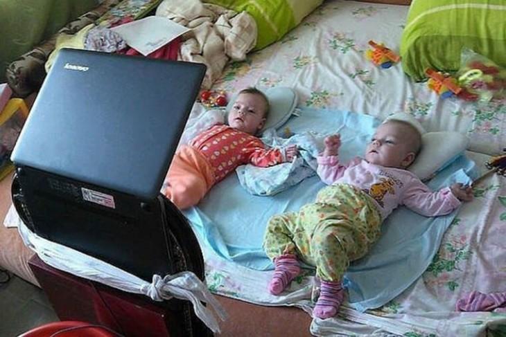 dos bebés acostadas en la cama viendo la computadora