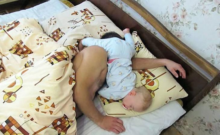 hombre dormido con su bebé sobre su cara