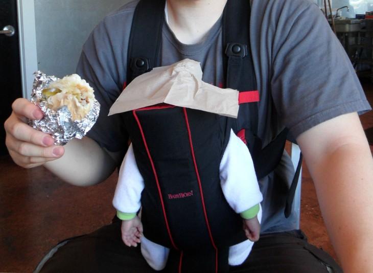 hombre comiendo sobre la cabeza de su bebé mientras lo trae en una cangurera