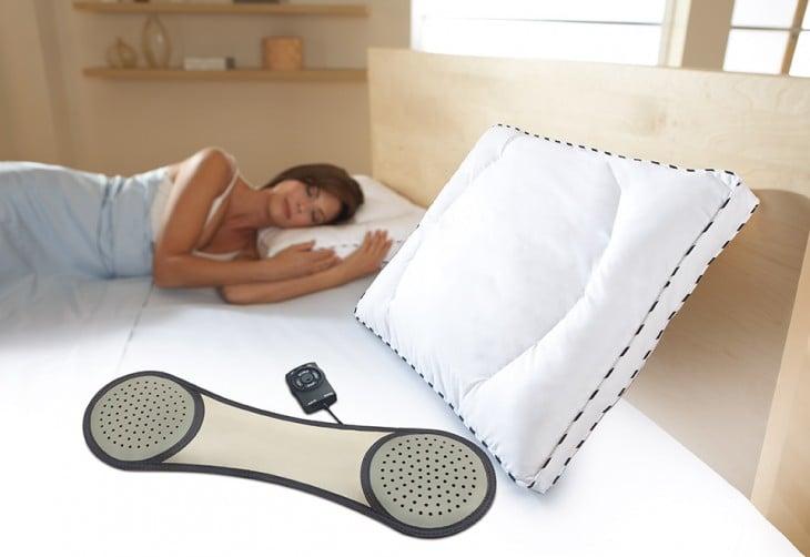 mujer acostada a lado de una almohada con un altavoz
