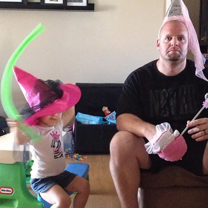 hombre disfrazado de princesa a lado de su pequeña hija
