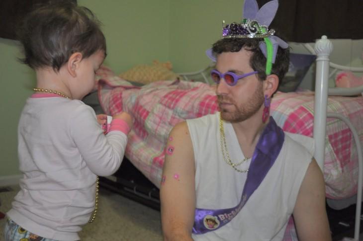 niña adornando a su padre con collares y coronas