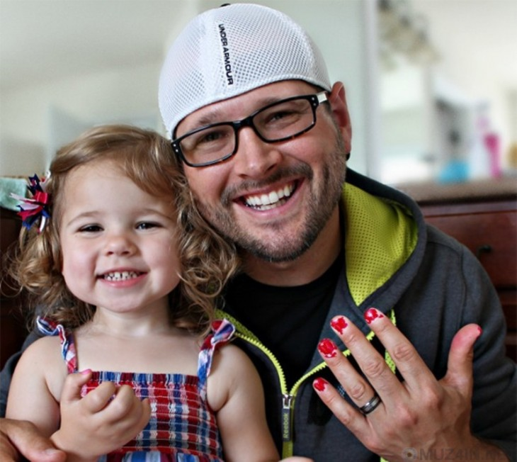 hombre sonriente mostrando sus uñas pintadas a lado de su hija