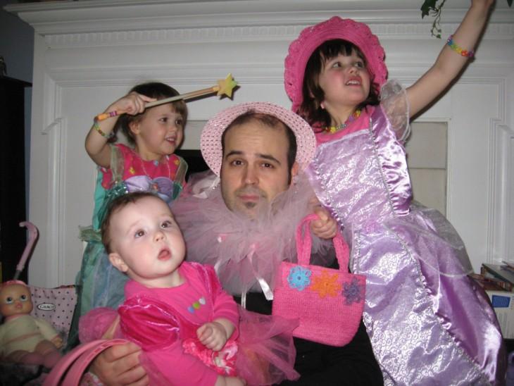 hombre con un sombrero rosa rodeado de sus tres hijas