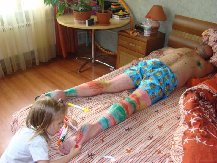 niña pintando a su papá mientras duerme