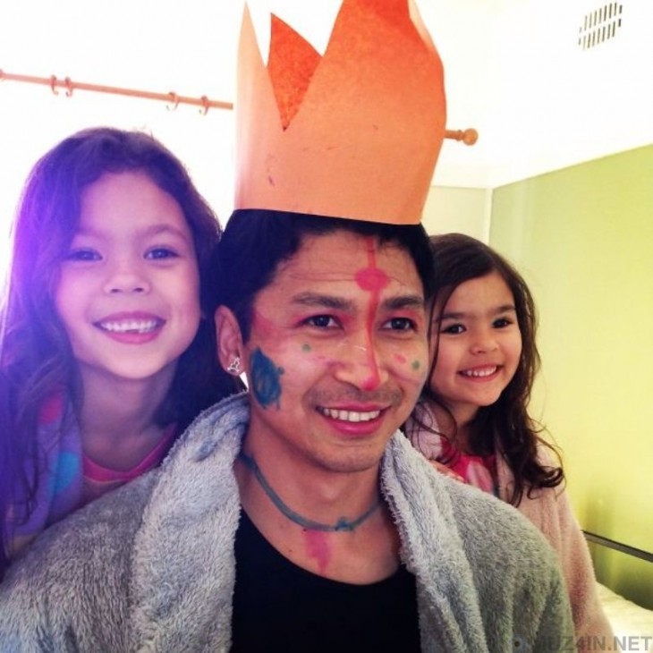 hombre en medio de sus dos hijas con la cara pintada y una corona de papel