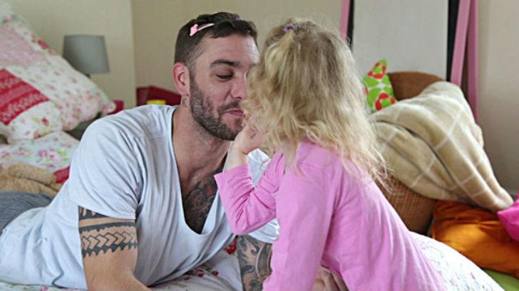 niña poniendo labial en los labios de su papá