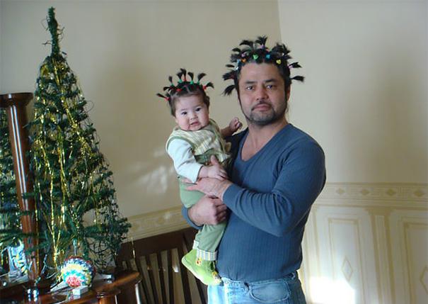hombre con colitas en el cabello cargando a su niña