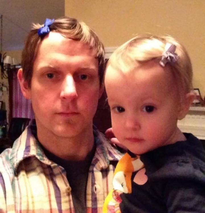 hombre cargando a su niña con el mismo peinado