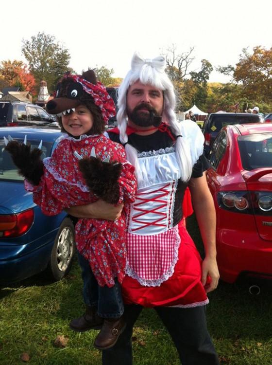 Hombre vestido de caperucita roja cargando a su hija vestida de hombre lobo