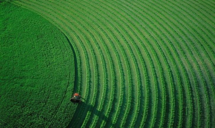tractor recorriendo unos pastos verdes con círculos