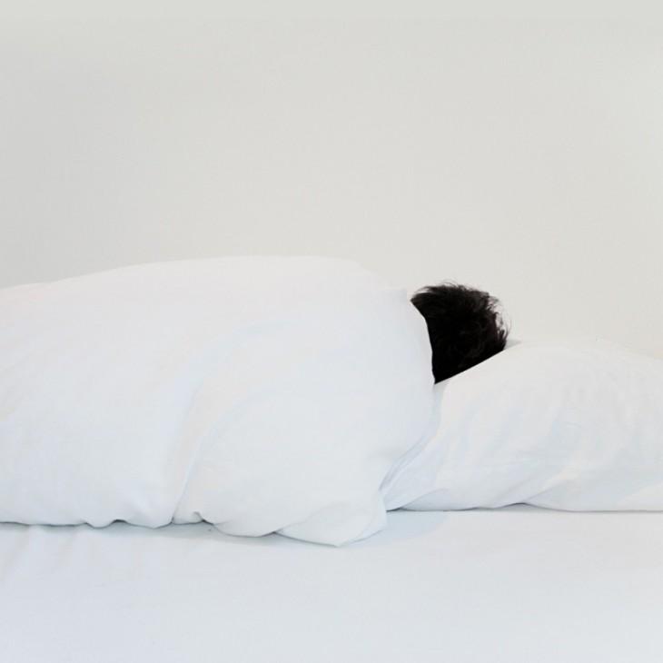 imagen de una persona acostada sobre sábanas blancas