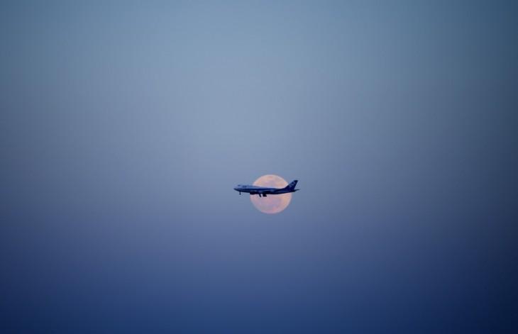 imagen de un avión pasando frente a la luna