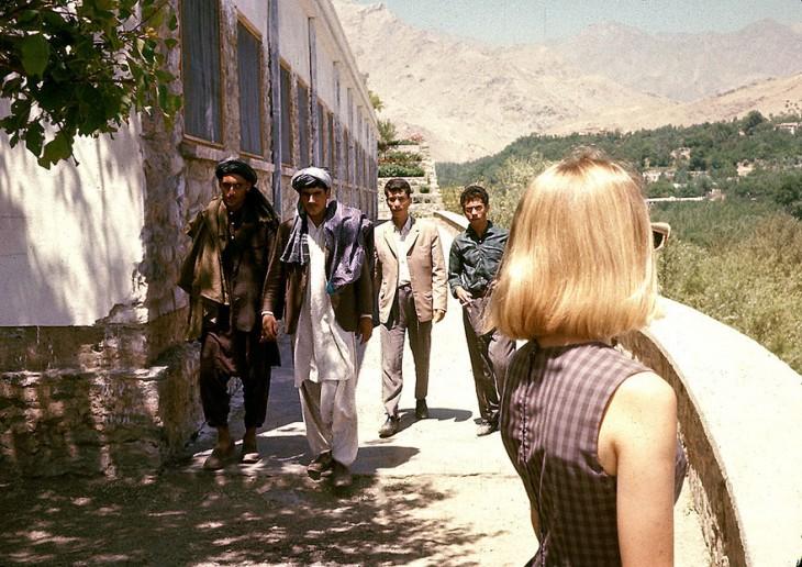 Chica mirando a unos hombres en una calle de Afganistán, 1960