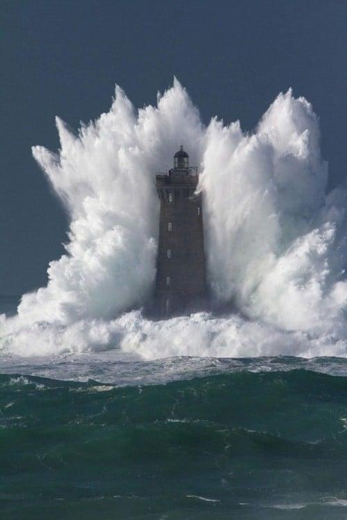 Fotografía de una ola chocando con una torre en el mar