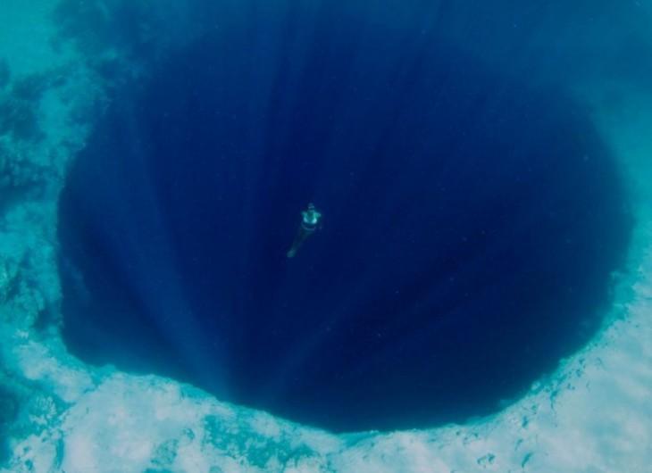Fotografía de una chica nadando cerca de un profundo abismo