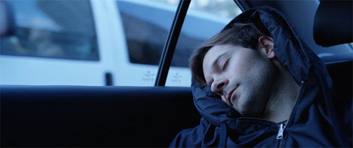 hombre acostado sobre la puerta de un carro en la sudadera Hypnos