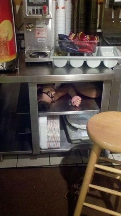 imagen de un hombre dormido debajo de una mesa