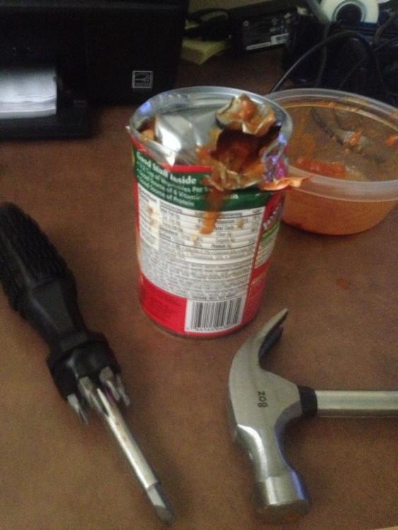 lata de comida abierta con un desarmador y un martillo
