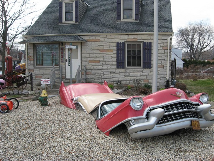 un coche sumergido en la parte delantera de una casa