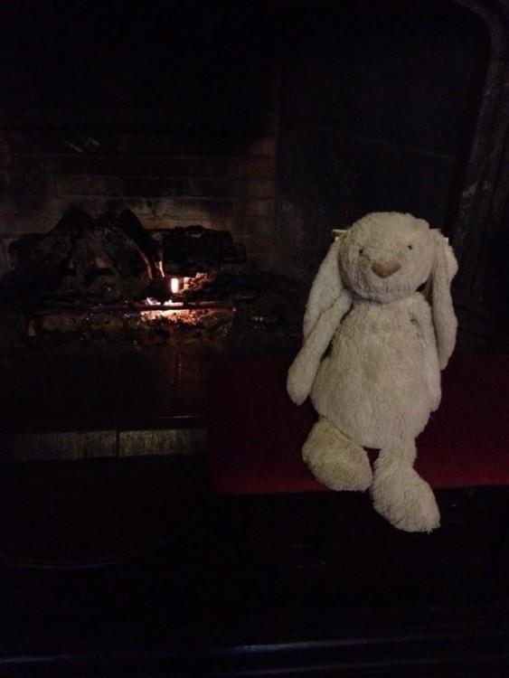 conejo de peluche sentado en una silla frente a una chimenea